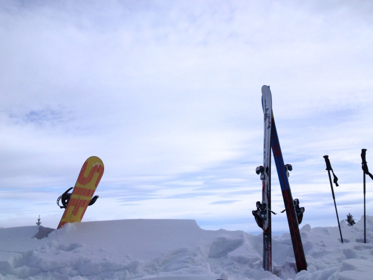 Skis, snowboard against the sky